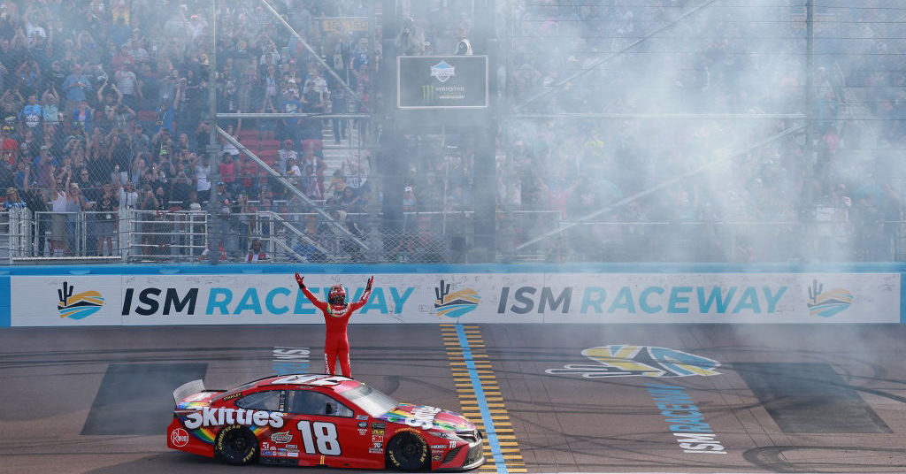Kyle Busch celebrates with the fans after winning the TicketGuardian 500 at ISM Raceway.