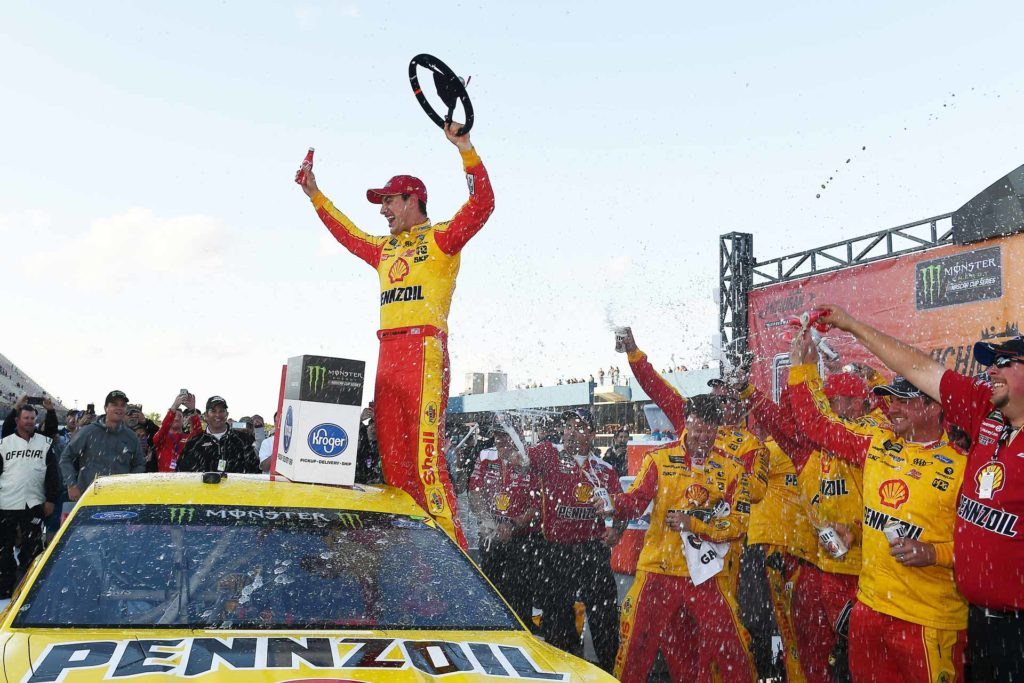 Joey Logano celebrates in victory lane after winning the Firekeepers Casino 400