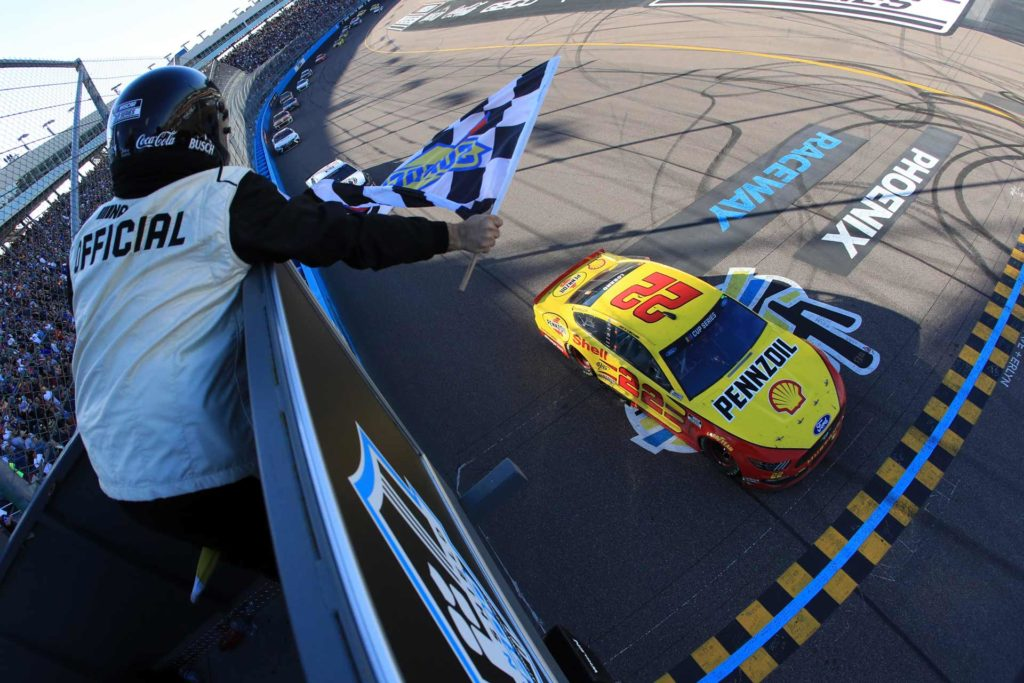 Joey Logano takes the checkered flag to win the FanShield 500 at Phoenix Raceway.
